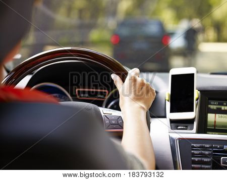 hand of a female holding the steering wheel of a vehicle with a cellphone mounted on the dashboard.