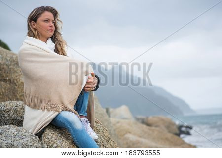 Thoughtful woman wrapped in shawl sitting on rocks at the beach