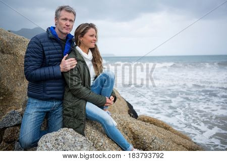 Couple sitting on rocks and enjoying the view at the beach