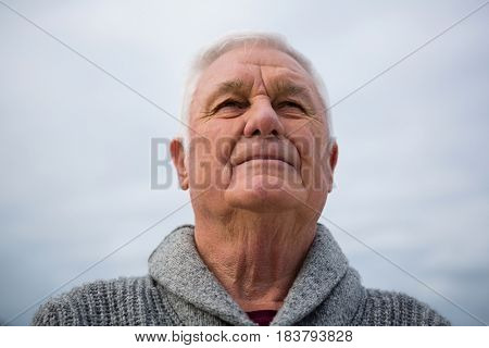Thoughtful senior man standing at the beach