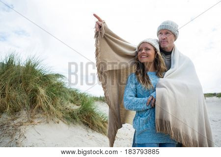 Happy mature couple pointing at view on beach