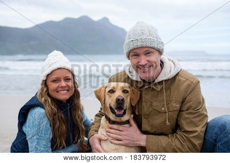 Portrait of smiling couple with pet dog at the beach