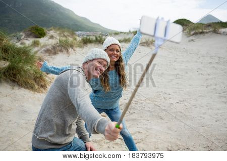 Happy couple taking a selfie from selfie stick at beach