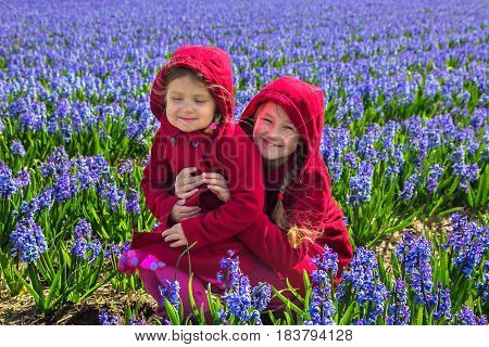 Two children in the flowering field of hyacinths. Two sisters embracing they are dressed in the same coat.