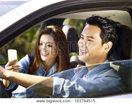 young asian couple enjoying ride in a car woman taking a selfie.