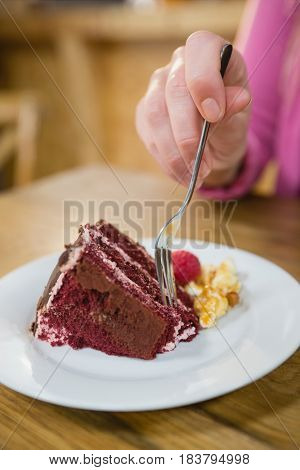Close-up of woman having pastry in café