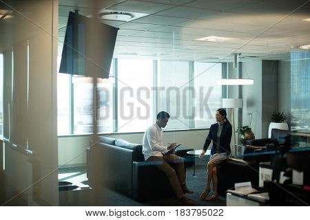 Businessman signing contract while sitting on sofa in office seen through glass