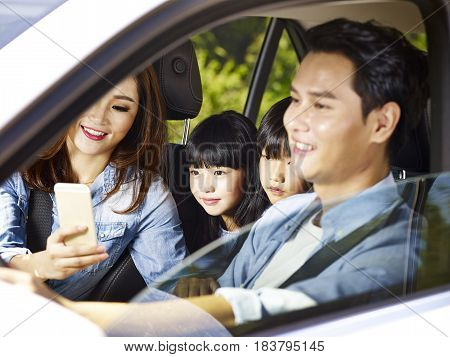 happy asian family with two children traveling by car mother using cellphone while father driving focus on the little girl.