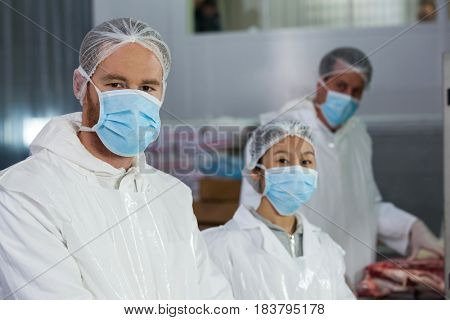 Portrait of butchers in protective workwear at meat factory