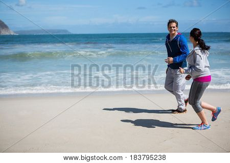Mature couple jogging on beach during winter season
