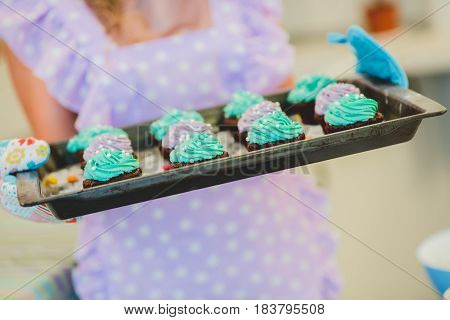 cupcakes are on the tray. Female hands holding dessert.Multi-colored cakes