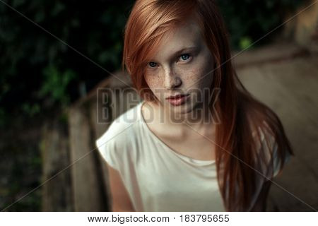 Closeup portrait of a young red-haired girl with freckles and blue eyes looking into the camera up horizontal photo