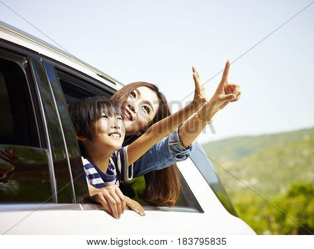 happy asian mother and son sticking heads out of rear window of a car looking at scenery.