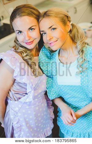 two happy women arm in arm in the kitchen dressed in aprons