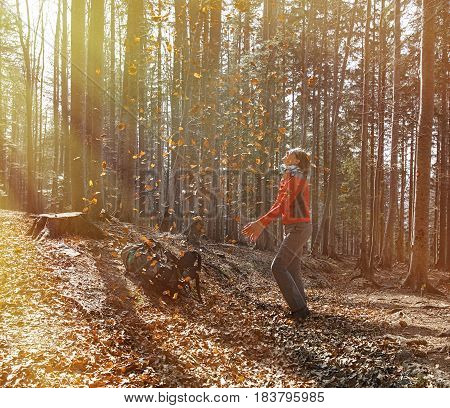 Athletic woman hiker enjoying the nature throwing leaves in autumn sunny forest. Nature lover active lifestyle happiness and fun concept.