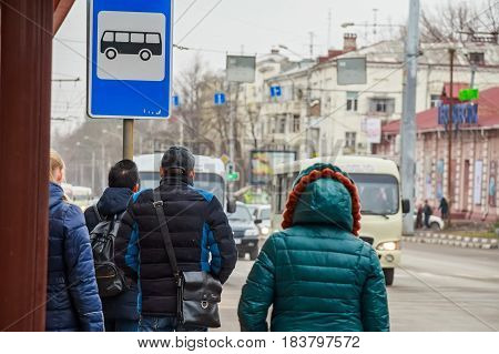 Back view of people in winter clothes waiting for bus and bus blue stop sign above them
