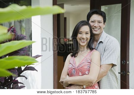 Japanese couple hugging on patio