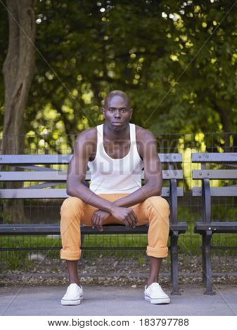 Serious African man sitting on bench