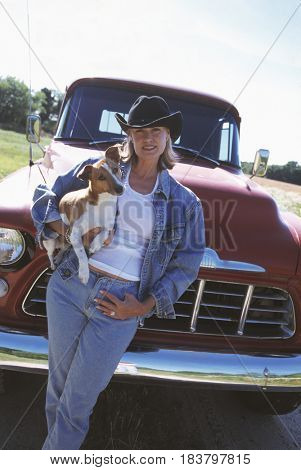 Woman wearing cowboy hat and holding dog