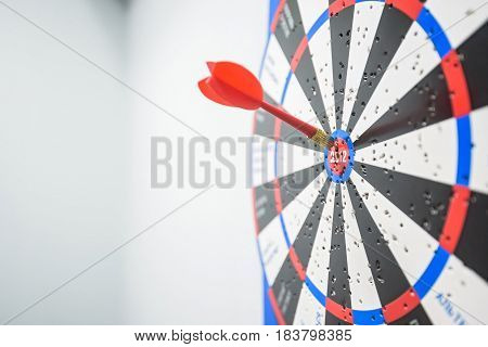 Closeup of red and blue dart board with dart arrows in center