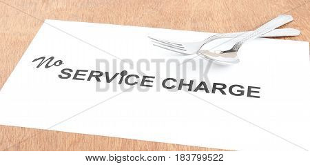 Service charge or tips concept indicated by text and steel fork and spoon.