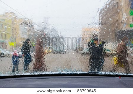 Blurry pedestrians silhouettes through windscreen covered in raindrops