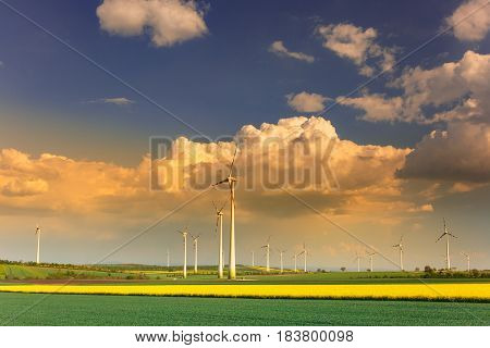 Wind farm with spinning wind turbines amidst agricultural land of intensive crop production in dramatic light. Sustainable and renewable power production ecology and environmental conservation concept.