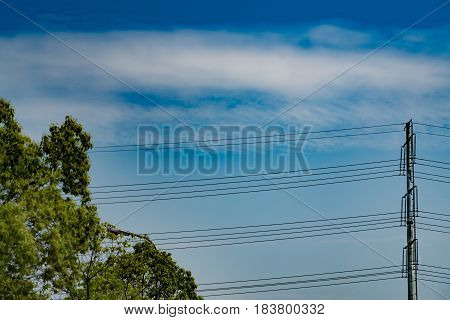 blue sky on sunny day with high voltage electric power supply pole