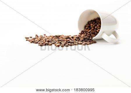 Roasted Coffee Beans Scattered Of Coffee Mug Isolated On White