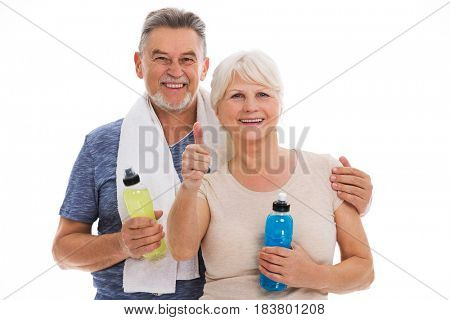 Fitness senior couple with towel and bottles