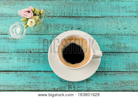 Top View Of Coffee Mug Steam And Flowers In Vase On Table