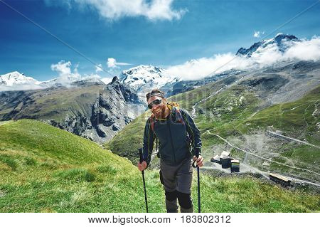 hiker on the trail in the Apls mountains. Trek near Matterhorn mount. Mountain ridge on the background