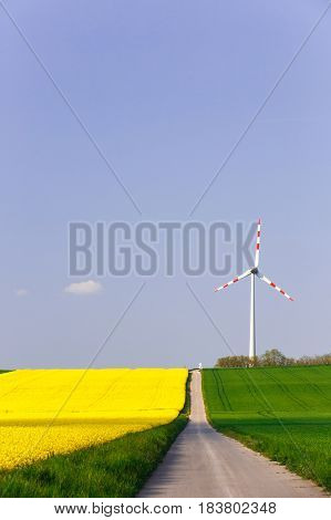 Wind farm with spinning wind turbine amidst agricultural land of intensive rapeseed production. Sustainable and renewable power production ecology and environmental conservation concept.