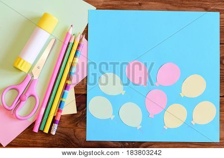 Creating a paper card with balloons. Step. Tutorial for children. Air day or birthday card concept. Card with balloons, scissors, glue stick, colored paper, pencils on a table. Children art activity