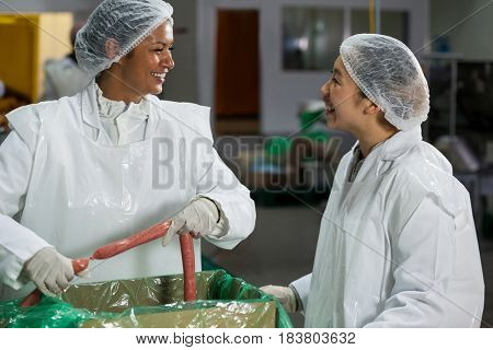 Female butchers processing sausages at meat factory