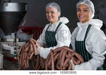 Portrait of female butchers processing sausages at meat factory