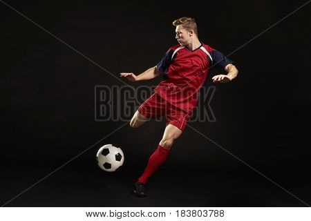 Professional Soccer Player Shooting At Goal In Studio