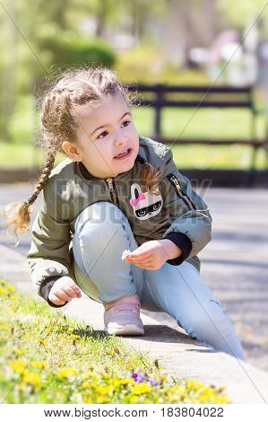 Cute little girl sitting in the spring grass with daisies