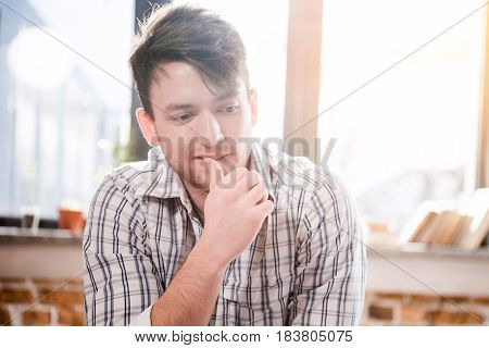 Young Thoughtful Man Owner Of Small Business Sitting With Hand On Chin And Looking Away