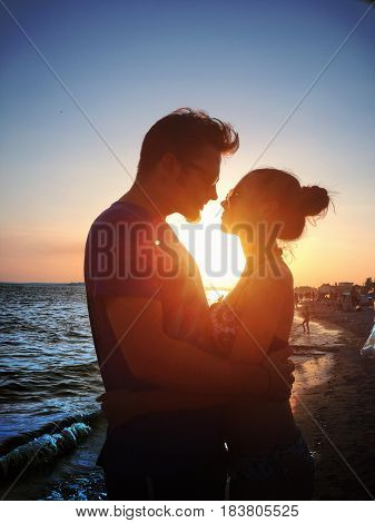Beautiful young couple looking in love at sunset on the sea beach