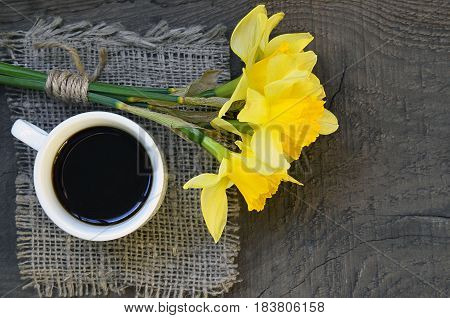 Coffee cup and bouquet of narcissus flowers on old rustic wooden table.Coffee mug and spring flowers.Spring morning,Breakfast,Good morning concept.Selective focus.