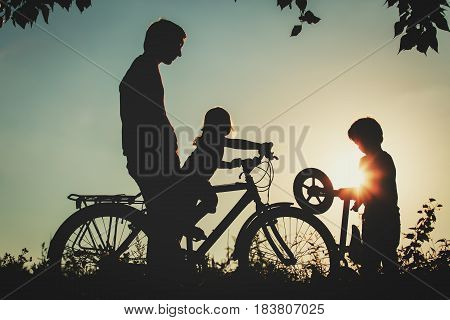 father with son and daughter riding bikes in sunset nature