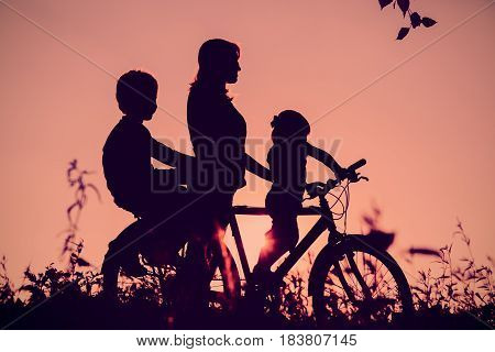 mother with son and daughter riding bike in sunset nature