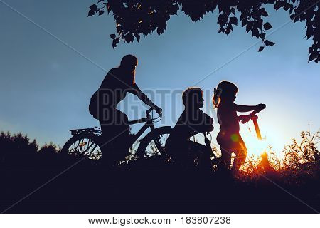 mother with son and daughter riding bikes and scooter in sunset nature