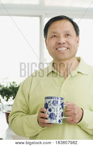Chinese man smiling and holding coffee cup