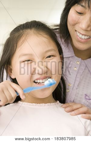 Chinese mother watching daughter brush teeth