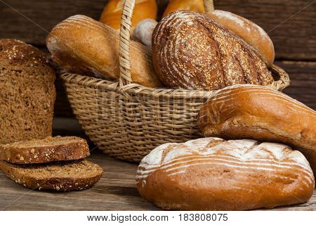 Various bread loaves in basket on wooden background