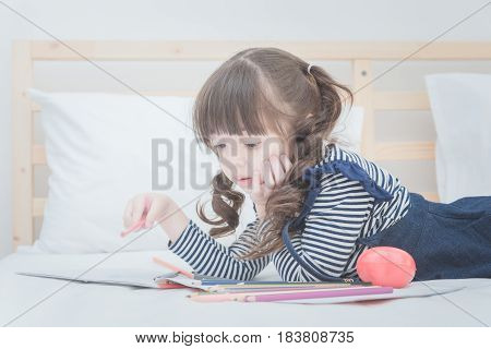 Cute Little Girl Doing Homework,writing And Drawing With Colourful Pencils On Bed At Home. Elegant D