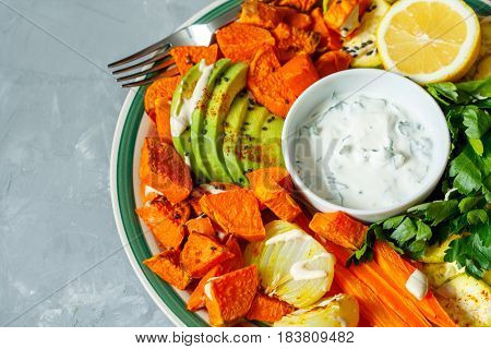 Baked sweet potato zucchini and carrots with sour cream sauce on a plate.