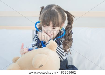 Cute Little Girl Enjoy Playing Doctor With Doctor Toy Set And Cute Doll While Sitting On Bed In Kid'